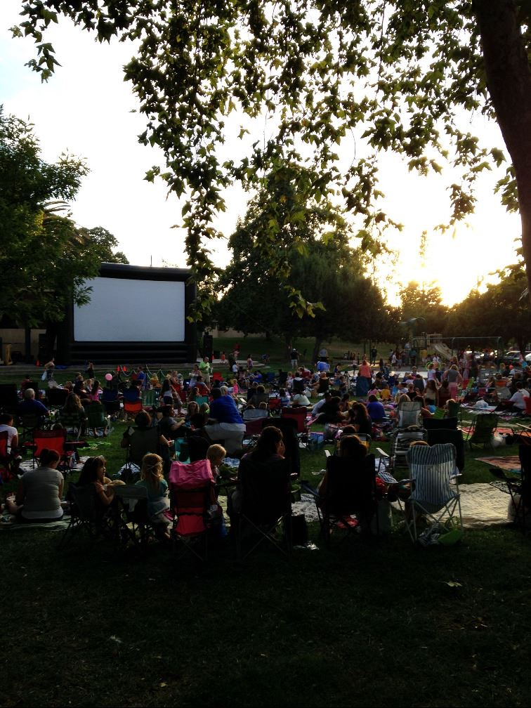 Crowd of People in Park with Large Outdoor Movie Screen