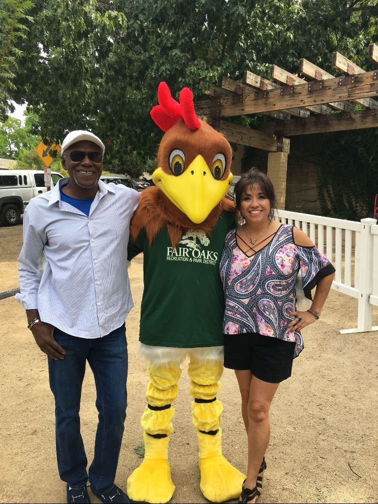 Two Adults posing with Mascot Rooster
