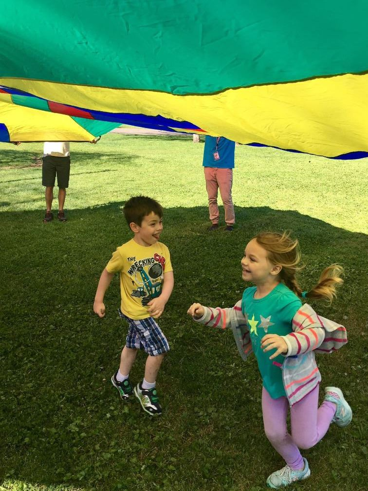 children playing under colorful parachute